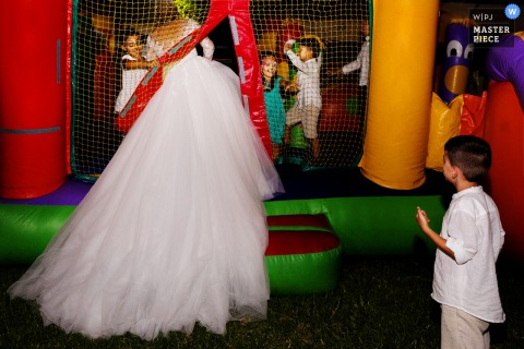 The bride gets into a bounce house with children in this photo by a Madrid, Spain wedding photographer.
