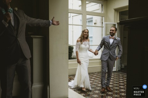 A man extends his hand to the bride and groom as they enter the reception in this photo by a North Yorkshire, England wedding reportage photographer.
