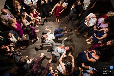 Zwei Männer liegen auf dem Rücken und treten mit den Beinen auf die Tanzfläche, während die Gäste auf diesem Foto eines Hochzeitsfotografen aus New Jersey zusehen.