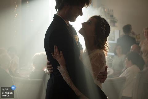 De bruid en bruidegom houden elkaar vast als licht schijnt tussen hen in deze foto door een Malopolskie, Polen huwelijksfotograaf.