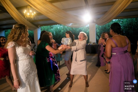 Photo of two women fighting over the bride's bouquet by a Knoxville, TN wedding photographer.