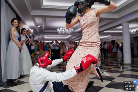 A man and woman wear boxing gloves and have a mock fight in this photo by a Krakow wedding photographer.