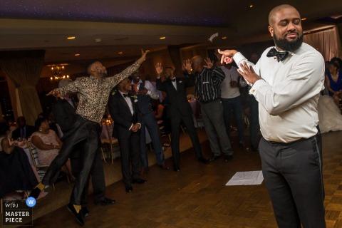 Foto des Bräutigams, der das Strumpfband weg von seinem Finger schießt, während ein anderer Mann in die Luft auf der Tanzfläche von einem Hochzeitsfotografen Baltimores, MD springt.