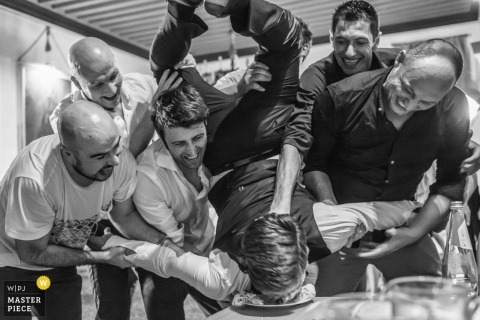 Black and white photo of men lifting up the groom and shoving his face into a plate of food by a Venice wedding photographer.