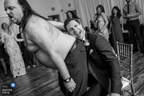 A Los Angeles, California wedding photograph of the groom sitting in a chair resting his head on a shirtless heavier-set man