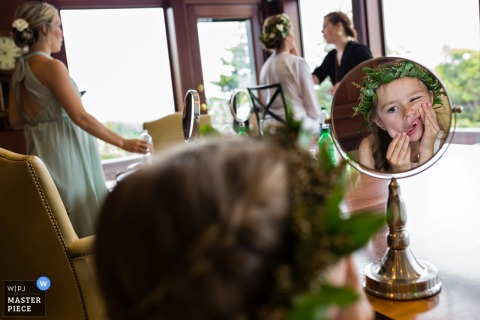 A girl makes faces in a mirror as two bridesmaids get ready for the ceremony in this photo by a Maine wedding photographer.