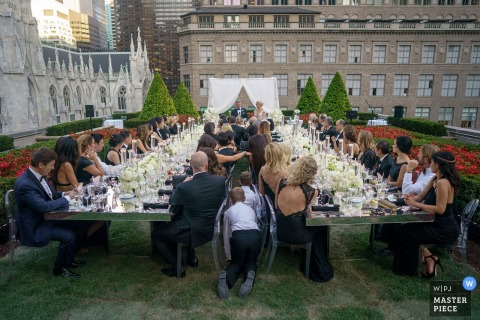 Two boys crawl between two long tables as guests sit outside for the reception in this photo by a Bronx, NY wedding photographer.