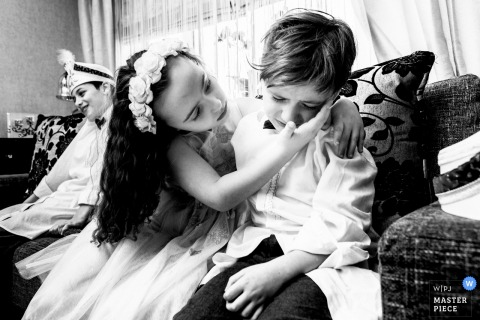 A concerned girl puts her arm around a little boy and cups his face with her hand in this black and white photo by a London, England wedding reportage photographer.