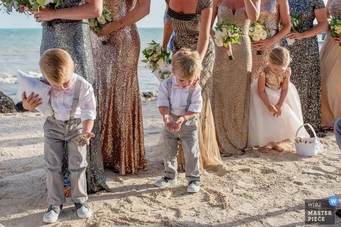 Drie kinderen, inclusief de ringdrager en bloemenmeisje, spelen met het zand op het strand tijdens de ceremonie terwijl ze bij de bruidsmeisjes op deze foto staan door een huwelijksfotograaf van Key West, FL.