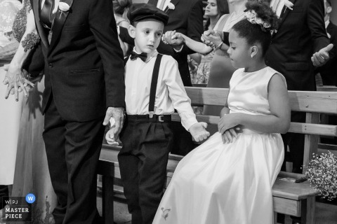 A young boy extends his hand to a girl when it's time to stand during the ceremony in this black and white photo by a Minas Gerais, Brazil wedding photographer.