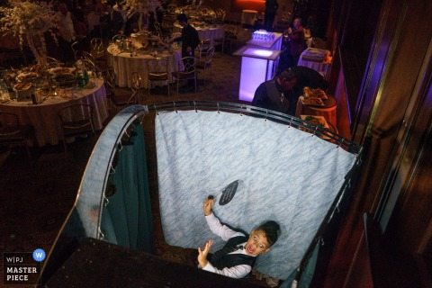 A young plays around behind a curtain as people work on setting up the reception hall in this photo by a Bronx, NY wedding photographer.