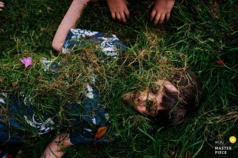 Een jongen ligt op de grond terwijl een ander kind hem bedekt met gras op deze foto door een trouwreportfotograaf uit Londen, Engeland.