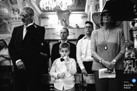 Guests stand for the ceremony while a young boy has his finger in his nose in this black and white photo by a Portofino wedding photographer.