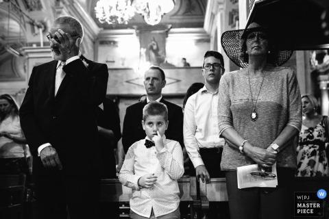 Auf diesem Schwarz-Weiß-Foto eines Portofino-Hochzeitsfotografen stehen die Gäste für die Zeremonie, während ein Junge den Finger in der Nase hat.