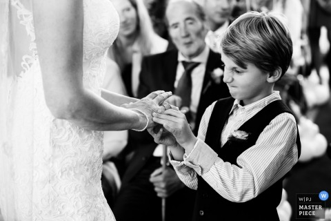 A boy struggles to take a ring off the bride's finger in this black and white photo by an Overijssel, Netherlands wedding photographer.