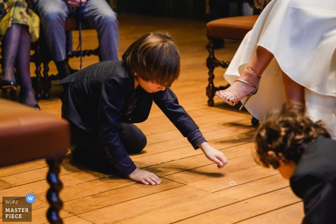 Detail photo of a young boy reaching for something on the ground. Taken by a Overijssel, Netherlands wedding photographer.