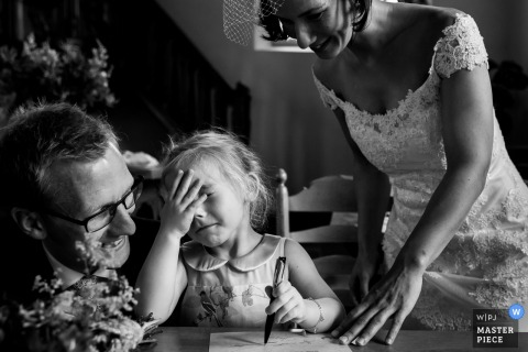 Black and white photo of the bride and groom with a little girl who is beginning to cry as she writes a letter by a Rotterdam wedding photographer.