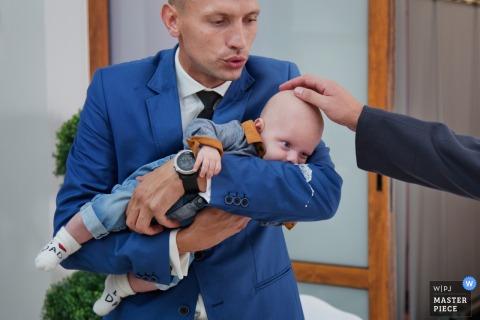 Foto eines Mannes, der ein Baby wiegt, während jemand den Kopf des Babys von einem Krakauer Hochzeitsfotografen berührt.