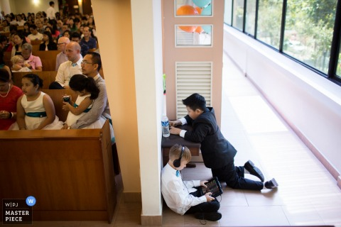 Photo of two young boys playing games on tablets during the ceremony by a Singapore wedding photographer.