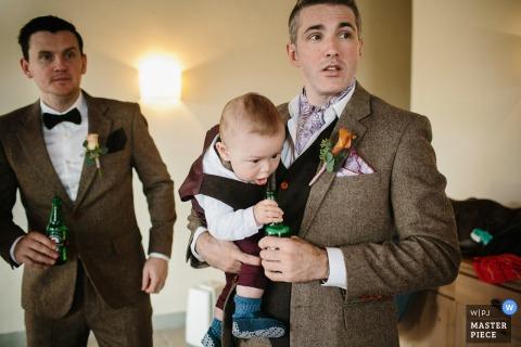 Foto eines Mannes, der ein Baby hält, das versucht, einen Schluck von der Bierflasche zu nehmen, die er von einem Portofino-Hochzeitsfotografen hält.
