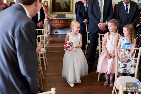 A Leicestershire, East Midlands wedding photo of the flower girl walking down the aisle as she looks at two little girls