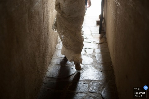 Detail photo of the bride walking down a narrow, stone street as she holds her dress up. Taken by a Manhattan, NY wedding photographer.