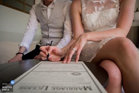 Foto di dettaglio della sposa e dello sposo firma la loro licenza di matrimonio. Preso da un fotografo di matrimoni di Denver, CO.