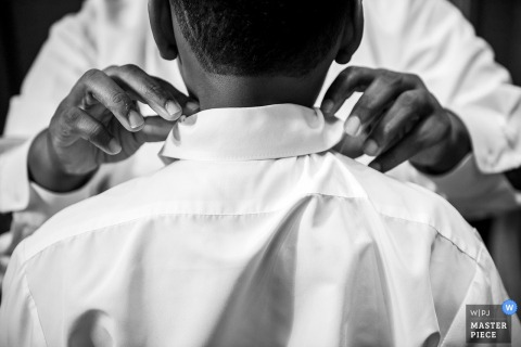 Detail photo of a man fixing a boy's collar as they get ready for the ceremony in this black and white photo by a Boulder, CO wedding photographer.