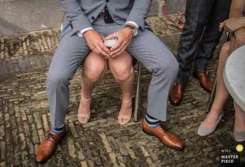 Detail photo of a man sitting on a woman's lap by a Netherlands wedding photographer.
