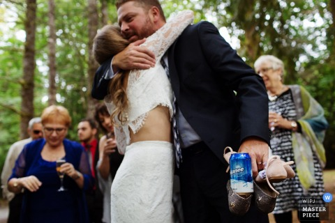 A man hugs the bride with one arm as he holds two pairs of shoes and a beer in the other hand in this photo by a Victoria, British Columbia wedding photographer.