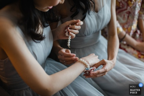 Detail photo of a woman helping another woman put her bracelet on. Taken by a Hong Kong wedding photographer.