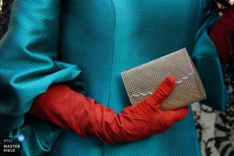 Detail photo of a woman in a blue dress with a red glove holding a small clutch. Taken by a Warsaw wedding photographer.