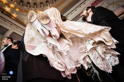 Detail photo of the bottom of the bride's shoes and dress as guests lift her up in this photo by a New Jersey wedding photographer.