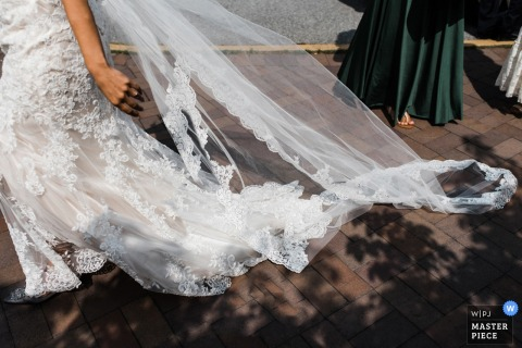 Foto de detalle del velo de la novia en el suelo detrás de ella con sombras de hojas. Tomado por un fotógrafo de bodas de la Columbia Británica, Canadá.