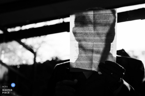 Black and white detail photo of a man's shadow visible through a letter he's reading. Taken by a Greater Manchester, England wedding reportage photographer.