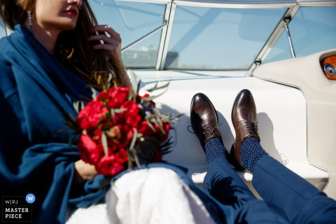 Detail photo of the groom's feet up on a bench next to the bride as they sit in a boat. Taken by a Saint Petersburg, Russia wedding photographer.