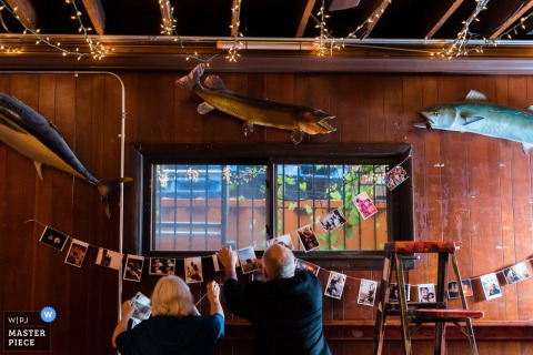 Detail photo of a man and woman decorating the reception hall with pictures by a Chicago, IL wedding photographer.