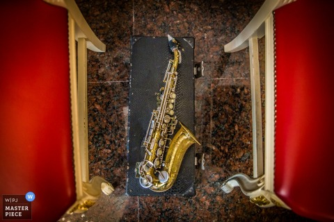 Detail photo of a saxophone sitting on top of its case in between two red chairs by a Sicily wedding photographer.