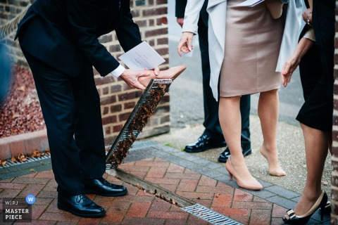 A West Midlands, England wedding photograph of a man attempting to get a woman's high heel out of a sidewalk grate
