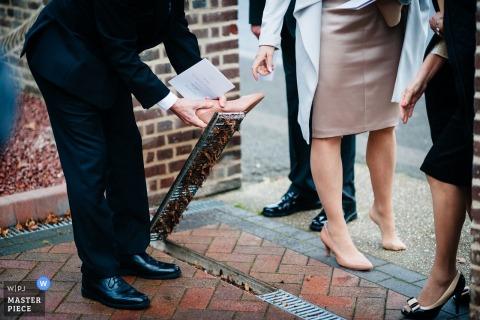 Photographie d'un mariage dans les Midlands de l'Ouest, en Angleterre, montrant un homme tentant de sortir le talon aigu d'une femme d'une grille de trottoir
