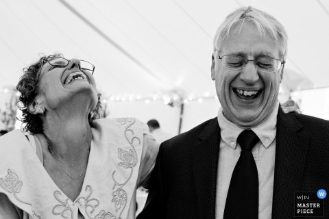 A man and woman can't stop laughing in this black and white photo by a Maine wedding photographer.
