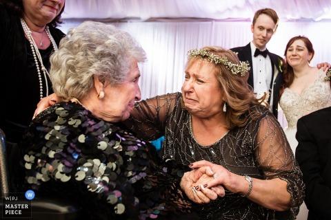 Zwei Frauen werden emotional und halten die Hände auf diesem Foto eines Hochzeitsfotografen aus New Jersey.