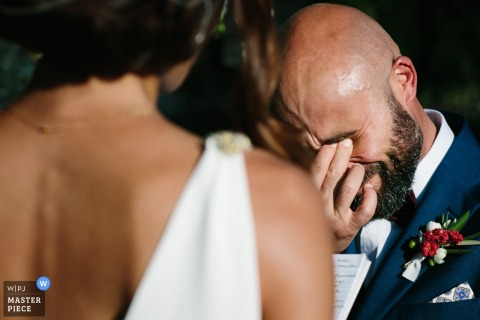 The groom tears up and covers his eyes with his hand when he sees the bride in this photo by a Portofino wedding photographer.
