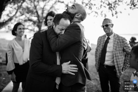 Schwarzweiss-Foto eines Mannes, der draußen den Bräutigam von einem Rom-Hochzeitsfotografen umarmt.