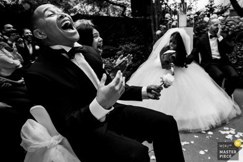 Photo en noir et blanc de la mariée et des invités riant tandis que le marié couvre son visage par un photographe de mariage à Rotterdam.