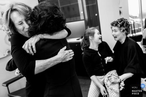 Deux femmes s'embrassent pendant qu'une fille et une femme portant des bigoudis rient dans cette photo en noir et blanc réalisée par un photographe de mariage à Rotterdam.