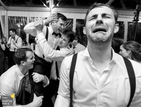 Black and white photo of a man crying in the foreground as others prepare to lift the groom behind him by a Chicago, IL wedding photographer.