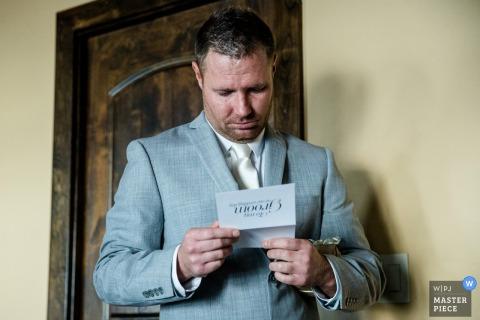 A Lake Tahoe, California wedding photo of a man in a grey tuxedo reading a note card