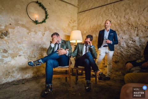 A Paris, France wedding picture of three guests in the corner of the room with two men sitting down and covering their faces with their hands while a third man is standing and  holding a drink in one hand while his other hand is in his pocket