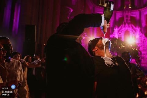 Ein Mann gießt während des Empfangs auf diesem Foto eines Hochzeitsreportagefotografen aus London, England, eine Flasche Champagner in den Mund eines anderen Mannes.